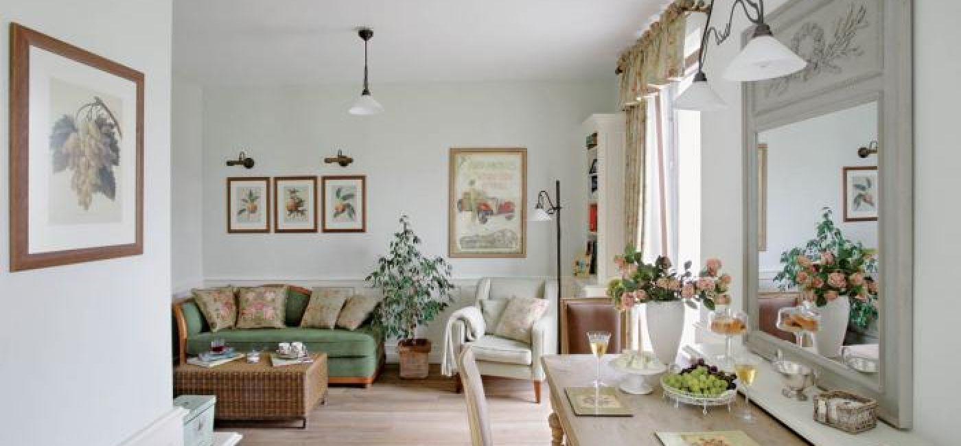 Na zielonej kanapie leżą poduszki obszyte tkaniną w róże.
