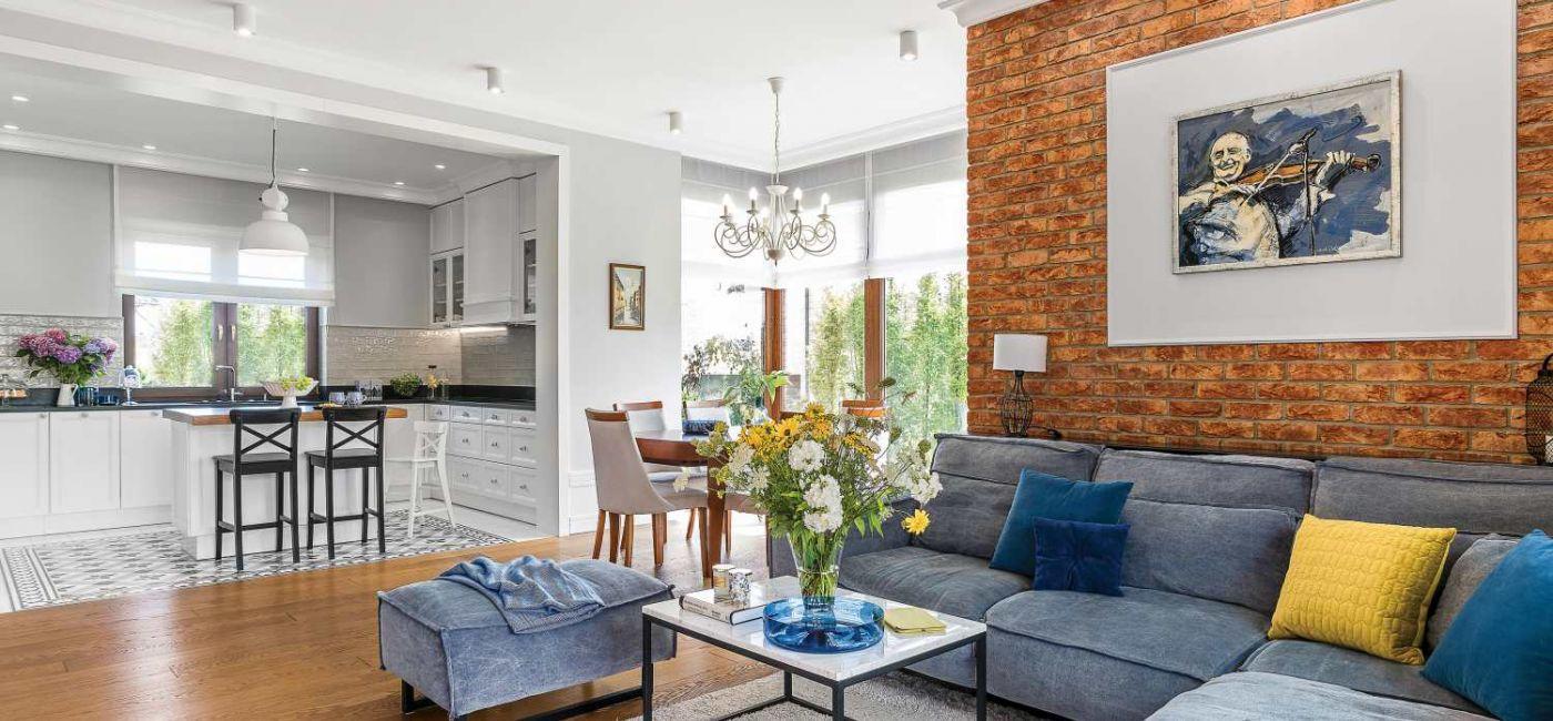 Salon zdobi ściana z cegieł, sypialnię – błękitne motywy. To dom trochę klasyczny, trochę nowoczesny,