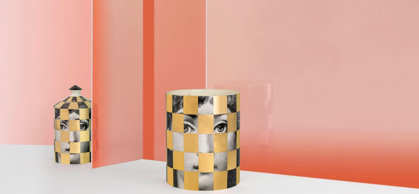 Świece zapachowe Golden Burlesque w porcelanowych pojemnikach dekorowanych motywami z twórczości Piero Fornasettiego,