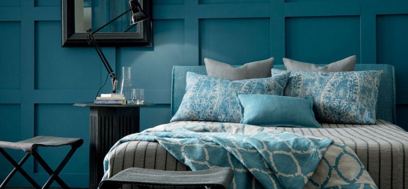 Pasy obok geometrycznych wzorów. Niebieskoszare wzorzyste tkaniny PERSIAN BLUE i SAVANNA CHARCOAL, narzuta JEPARA ATLANTIC,