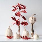 białe dynie i jesienne liście na złotych wazonikach i świecznikach