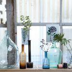 Butelki-flakony z kolorowego szkła będą efektowną dekoracją zarówno mieszkań w chłodnym stylu skandynawskim, jak i