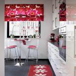 Chłodna biel szafek i płytki na podłodze łagodzą intensywną czerwień.
