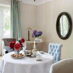 Chłodny błękit pikowanego fotela i zasłon przełamują ciepłe biele, beże i ecru.