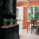 Ciemny kredens kontrastuje z jasną kuchnią.