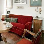 Czerwona kanapa i fotel zachęcają do chwili przerwy przy okrągłym stole.