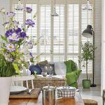 Dominującą biel przełamują delikatne zielenie oraz kolory dekoracji - także sezonowych kwiatów w wazonie.