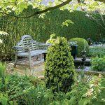 Drewniana, romantyczna ławka. Tulipany wśród bukszpanów
