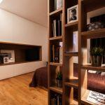Drewniany regał na książki oddziela najbardziej intymną część sypialni od wejścia.
