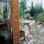Drewniany taras otacza ogród pełen drzew i kwiatów.