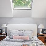 Kameralna sypialnia pod skosami z widokiem na las. Futro i poduszki to BBHome.