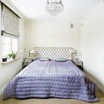 Lawendowa narzuta w sypialni przełamuje jasne kolory ścian.