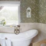 Łazienka na parterze wygląda jak mały włoski salon kąpielowy. To zasługa romantycznej tapety.