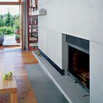 Minimalistyczny kamienny kominek komponuje się z drewnianą podłogą.