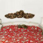Nad łóżkiem wisi płaskorzeźba przedstawiająca puttę.