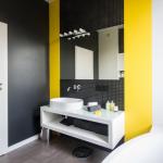 Nowoczesną i monochromatyczną aranżację łazienki dynamizują żółte pasy między płytkami.