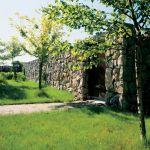 Ogród od drogi odgradza mur z kamienia. Widoku na łąki i pola i las nic nie zasłania.