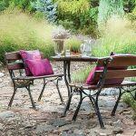 Proste meble ogrodowe i kolorowe, eleganckie poduszki.