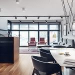 Salon umeblowano w proste meble. Pomieszczenie doświetla naturalne światło wpadające przez loftowe okna.