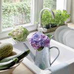 Świeże zioła w doniczkach na parapecie i warzywa i kwaty hortensji - ulubienicy pani domu.