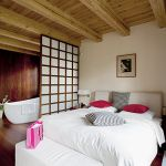 Sypialnia jest oddzielona od łazienki delikatnym przepierzeniem zrobionym z drewna i matowego szkła.