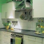 W kuchni wrażenie świeżości i przestrzeni dają proste białe szafki i chłodna zieleń ścian.