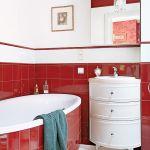 W łazience czerwień kafelków przełamana jest stylowymi białymi meblami.