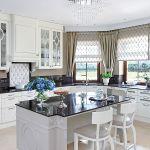 W pałacowej kuchni te same wzory co w salonie: elipsy na frontach szafek i ażurowe wstawki z błyszczacego metalu,