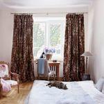 W sypialni biel i ecru rozpraszają brązowe zasłony i delikatne róże.