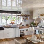 Proste szafki, dodatki z surowego drewna i wikliny, do tego eleganckie kamienne blaty i loftowe lampy.