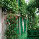 Zielone okiennice i elementy małej architektury ogrodowej sprawiaj, że dom wtapia się w ogród.