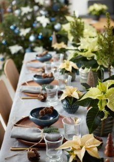 Drewno, ceramika, błyszczące złote sztućce, szyszki i gałązki tworzą aranżację na tym świątecznym stole, która