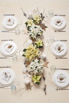 Dekoracja stołu z gwiazdami betlejemskimi w roli głównej. Ustaw na stole poinsecje w różnych odcieniach bieli i kremu w