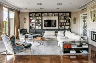 Dizajnerska lampa Arco Achille Castiglioniego w klasycznym towarzystwie foteli firmy Chelini i kanapy Flexform.