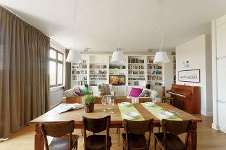 Duży rodzinny stół stoi między kuchnią a salonem.