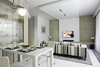 Centralna ściana w salonie wykończona została naturalnym drewnem, które stanowi motyw przewodni całego projektu. Ciekawym