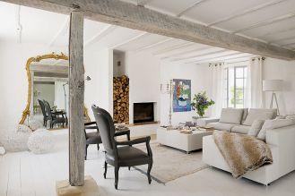Prosty salon ożywiają: bogate lustro, czarne ludwiki, kandelabr i obraz Jeana de Paula.