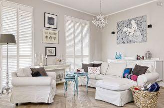 Tłem dla sztuki są białe ściany i jasne meble.