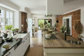 biała kuchnia z drewnem i czerwoną cegłą