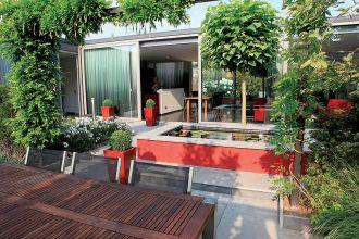 Czerwone akcenty w ogrodzie nawiązują do mebli w kuchni. Zielone kule w wysokich donicach to strzyżony bukszpan. W sadzwce