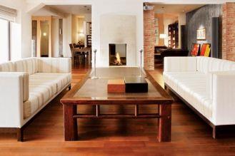 Dobre towarzystwo: betonowe ściany, kominek z piaskowca, podłoga z merbau. Wnęka na drewno przypomina dzieło