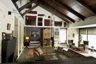 Salon z kamienia i drewna z otwarty stropem.