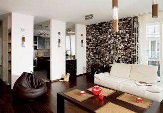 Biała kanapa i brązowy puf. Apartament na luzie