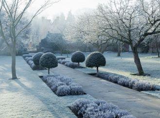 Wejście do tajemniczego, zimowego ogrodu prowadzi przez półokrągłą furtę