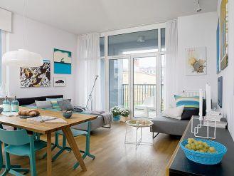 Salon urządzony jest minimalistycznie. Biel i szarości urozmaicają turkiusowe dodatki.