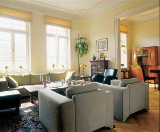 W salonie kanapa i fotele. Mieszkanie w stuletniej kamienicy