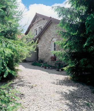 Kamienny dom pośród świerkowego lasu.