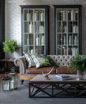 Ciemny kolor mebli w salonie warto przełamać jasną tapicerką sofy i np. wzorzystymi poduszkami.