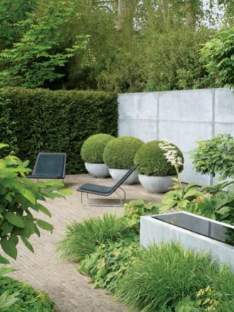 Betonowe mury, donice, oczko wodne - ocieplą je ozdobne trawy i strzyżone bukszpany.