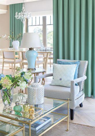 Lampa na stoliku, poduszki i ceramika dekoracyjna ze sklepu Mint Grey, dywan z House More, kwiaty z Karmon-decor.pl